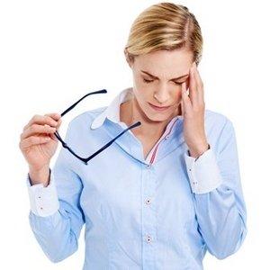 femme en chemise qui enlève ses lunettes et se tient la tête